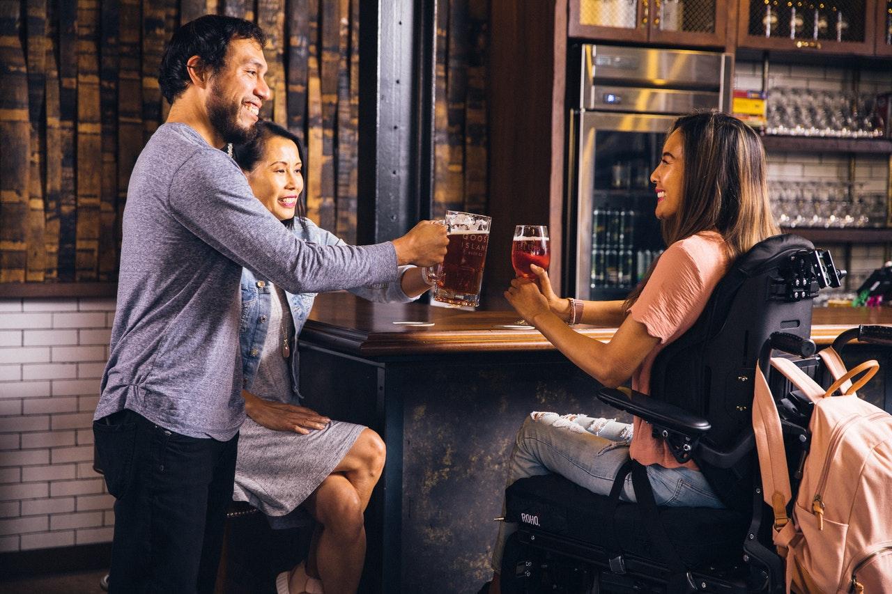 Rollstuhlfahrerin in einer Bar mit Freunden